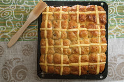 Top view of homemade easter hot cross buns on baking pan against colorful tablecloth Stock Images