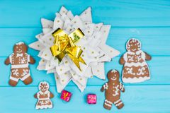 Top view of homemade gingerbread Christmas tree with cute ginger. Bread family with gifts on blue wooden desk. Mockup for seasonal offers and holiday post card Royalty Free Stock Photo