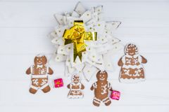 Top view of homemade gingerbread Christmas tree with cute ginger. Bread family with gifts on white wooden desk. Mockup for seasonal offers and holiday post card Royalty Free Stock Image
