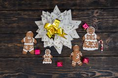 Top view of homemade gingerbread Christmas tree with cute ginger. Bread family with small gifts on wooden desk. Mockup for seasonal offers and holiday post card Stock Images