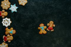 Gingerbread men and snowflakes. Top view of homemade gingerbread men and snowflakes with icing on black tabletop Royalty Free Stock Image