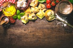 Top view on homemade pasta ravioli on old wooden table. With flour, basil, tomatoes and vintage kitchen accessories Stock Photo