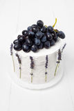 Top view of the homemade sour cream cake decorated with grapes and lavender on a white wooden background Stock Images