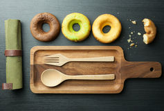 Top view of homemade three donuts and a haft donut on wooden pla Royalty Free Stock Images