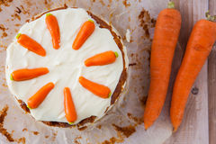 Top view of a homemane carrot cake with mascarpone cream cheese. Icing and handmade mini marzipan carrot decorations Stock Photos
