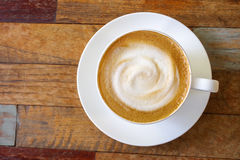 Top view of hot coffee cappuccino cup with milk foam on wood tab Stock Image