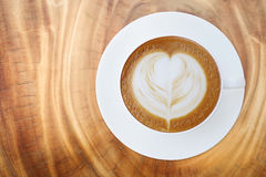 Top view of hot coffee cappuccino latte cup with saucer on wood Royalty Free Stock Images