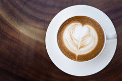 Top view of hot coffee cappuccino latte cup with saucer on wood Royalty Free Stock Photo