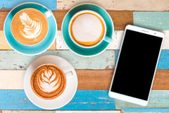 Top view hot Coffee in cup and Smart phone on Wooden table. royalty free stock images