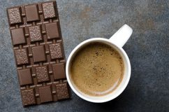 Chocolate bar and delicious cup of coffee on dark table,top view stock image