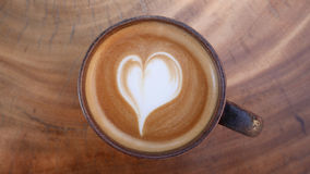 Top view of hot coffee latte art heart shape foam on wood table Royalty Free Stock Images
