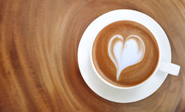 Top view of hot coffee latte art heart shape foam on wood table Royalty Free Stock Image
