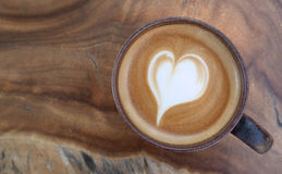 Top view of hot coffee latte art heart shape foam on wood table Stock Images