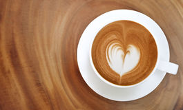 Top view of hot coffee latte art heart shape foam on wood table Royalty Free Stock Photos