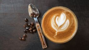 Top view of hot coffee latte art with coffee beans and spoon on wood table background Stock Photos