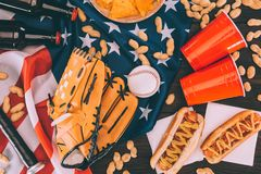 Top view of hot dogs, plastic cups, peanuts, beer bottles, baseball ball and glove with bat. On american flag stock photos