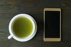 Top View of Hot Matcha Green Tea with an Empty Screen Smartphone on Dark Brown Wooden Table. Texture background antioxidants beverage black break business cafe stock image