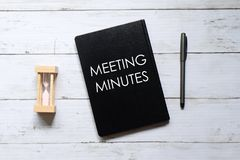 Top view of hour glass,pen and notebook written with 'MEETING MINUTES' on white wooden background.  royalty free stock photography