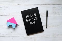 Top view of house model,pen and notebook written with 'HOUSE BUYING TIPS' on white wooden background.  Royalty Free Stock Photo