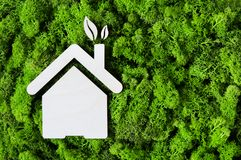 Eco green house concept. Top view of house wooden shape on green moss with copy space. High angle view of eco house and leaves. Environmental protection and Royalty Free Stock Photography