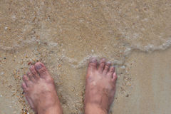 Top view and human feet on the sand and waves sea in the summer Stock Photos