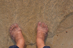 Top view and human feet on the sand and waves sea in the summer Royalty Free Stock Photography
