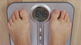 Top view human foot stepping on weighting scale for measuring body mass