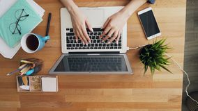 Top view of human hands touching laptop keyboard typing in office. Top view of human female hands touching laptop keyboard typing in office working using stock video footage