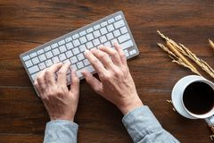 Top view of human hands typing on keyboard, wood desk stock image