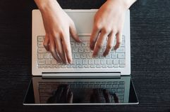 Top view of human hands typing on laptop royalty free stock image