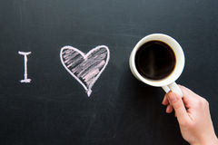 Top view of I love heart doodle drawing on chalkboard. With human hand holding cup of coffee royalty free stock photography