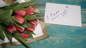 Top view of a I love you message note and Tulips flowers bouquet on a wooden table. Couple relationship concept. St. Valentine s Day. 4 k stock video footage