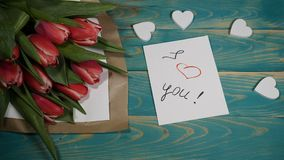 Top view of a I love You message note and Tulips flowers bouquet on a wooden table. Love relationship concept. St. Valentine s Day. 4 k stock footage