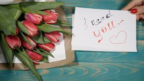 Top view of a I Need You message note and tulips flowers bouquet on a wooden table. Love relationship concept. Saint. Valentines Day. 4 k stock video