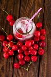 Top view on ice cubes in jar and cherries around Royalty Free Stock Image