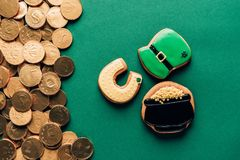 Top view of icing cookies and golden coins on green, st patricks day concept stock photography