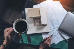 Top view image of an architects thinking and designing mass model while drinking hot coffee with shop drawing paper. And laptop on table royalty free stock photography