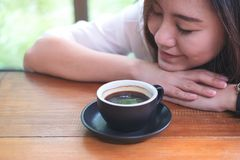 Asian woman sit with chin resting on her hands and closing her eyes smelling hot coffee on wooden table with feeling good in cafe. Top view image of Asian woman Royalty Free Stock Photos