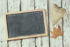 Top view image of autumn leaves and fabric heart next to chalkboard over wooden textured background. copy space Royalty Free Stock Images