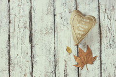 Top view image of autumn leaves and fabric heart over wooden textured background. copy space Royalty Free Stock Photography