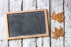 Top view image of autumn leaves next to chalkboard over wooden textured background. copy space Stock Photography