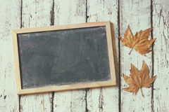 Top view image of autumn leaves next to chalkboard over wooden textured background. copy space. faded retro filtered image Royalty Free Stock Images