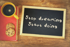 Top view image of blackboard with the phrase stop dreaming start doing, next to coffee cup and cookies Royalty Free Stock Images