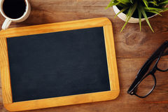 Top view image of blank chalkboard next to cup of coffee. On wooden table. ready for adding text or mockup Royalty Free Stock Photo