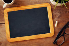 Top view image of blank chalkboard next to cup of coffee. On wooden table. ready for adding text or mockup Stock Photos