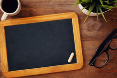 Top view image of blank chalkboard next to cup of coffee. On wooden table. ready for adding text or mockup Stock Photo