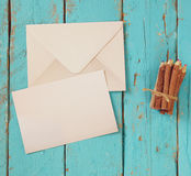 Top view image of blank letter paper and envelope next to colorful pencils on wooden table. vintage filtered and toned Royalty Free Stock Photo