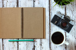 Top view image of blank notebook, cup of coffee and old camera Stock Photos