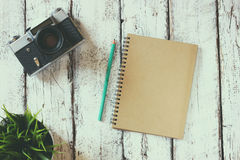 Top view image of blank notebook, cup of coffee and old camera Stock Image