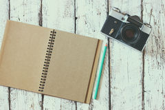 Top view image of blank notebook, cup of coffee and old camera Stock Photography